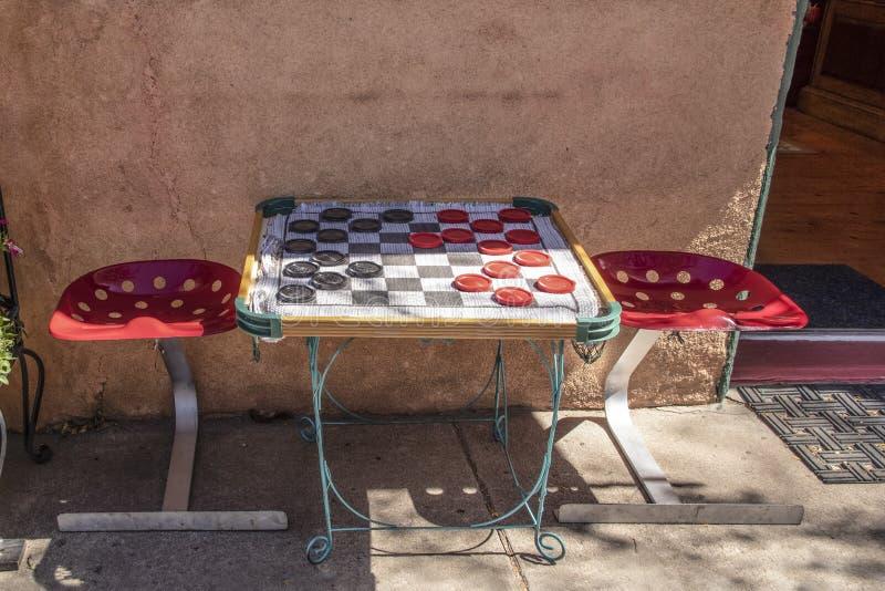 Таблица тротуара со стульями места трактора и половик шахматной доски с гигантскими контролерами сидя около стены штукатурки и от стоковая фотография rf