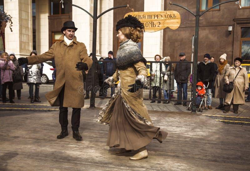 Танцы танцев человека и женщины винтажные в ретро костюмах на праздненствах Maslenitsa на квадрате Manezhnaya в Москве, стоковое фото rf