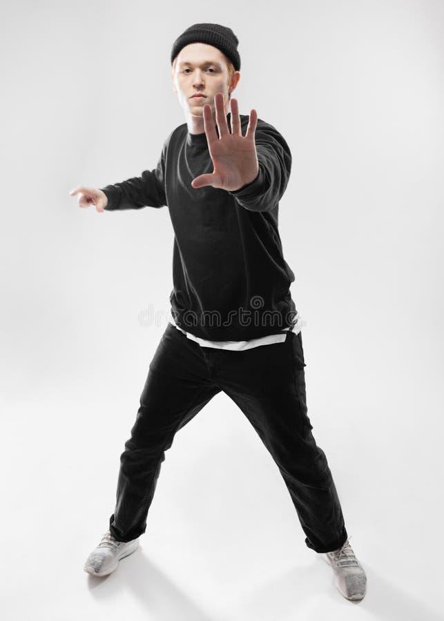 Танцор фристайла одетый в черных джинсах, фуфайке, шляпе и серых тапках танцует в студии на белизне стоковые фотографии rf