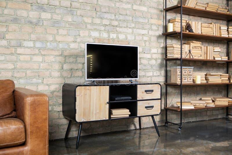 ТВ в интерьере в стиле просторной квартиры на прикроватном столике стоковое фото rf