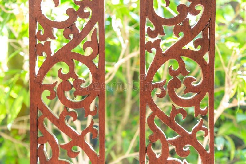 текстура Mahogany загородка с высекаенными картинами На предпосылке зеленого bushesTexture Mahogany загородка с высекаенными карт стоковое фото rf