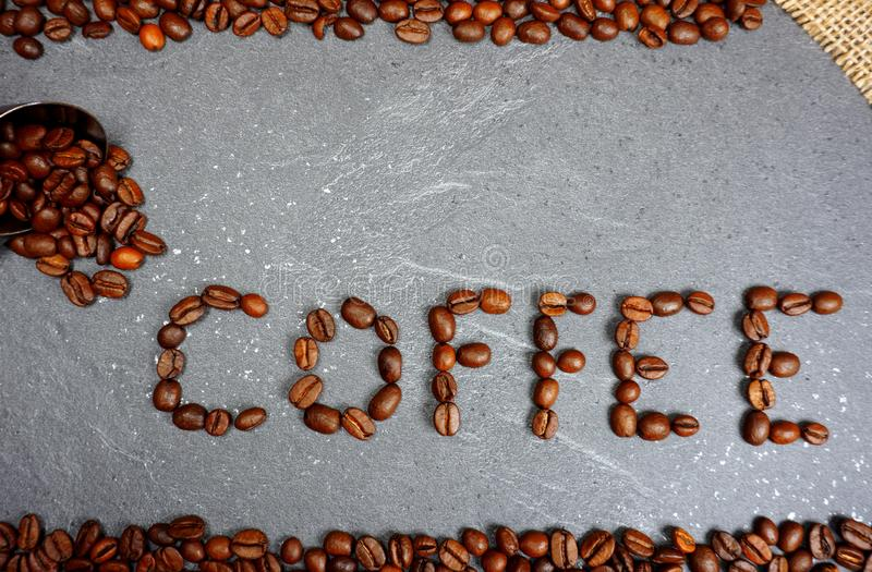 Текст от кофейных зерен справедливой торговли с мешковиной и ложкой на серой предпосылке worktop кухни стоковые изображения rf