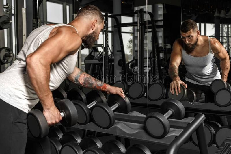телохранителя Бородатый человек работая на спортзале с гантелью смотря зеркало проверяя взгляд со стороны метода стоковые фото