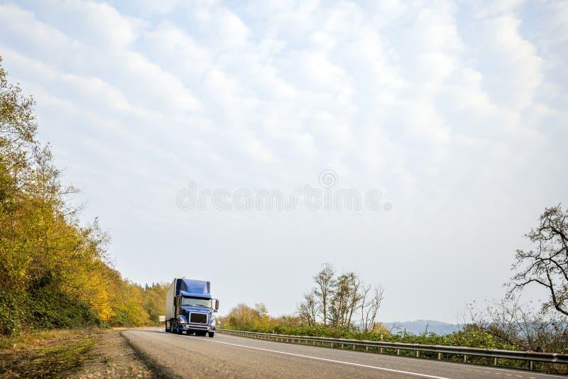 Темно-синего долгого пути большая снаряжения тележка semi с semi ходом трейлера на обматывая дороге осени стоковые фотографии rf