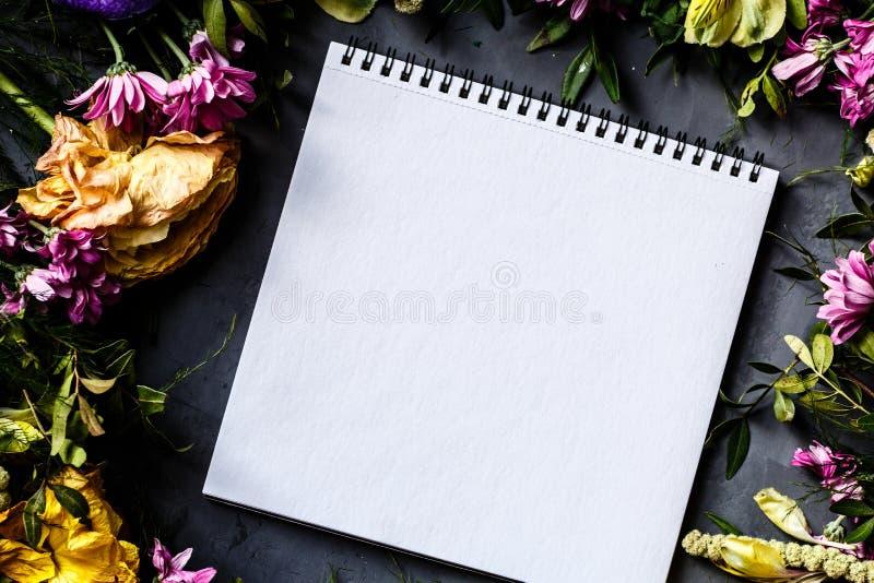 Тетрадь и букет ярких цветков для женщин дня, предпосылки дня матери Плоское положение Взгляд сверху стоковое фото