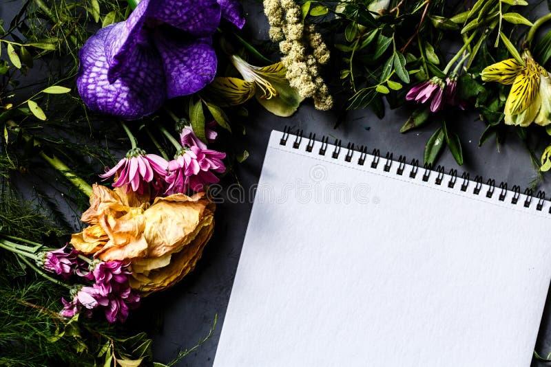 Тетрадь и букет ярких цветков для женщин дня, предпосылки дня матери Плоское положение Взгляд сверху стоковые фото