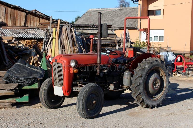 Тяжело - использовал старый винтажный ретро красный трактор окруженный со строительным материалом и отбросом в задворк стоковые изображения rf