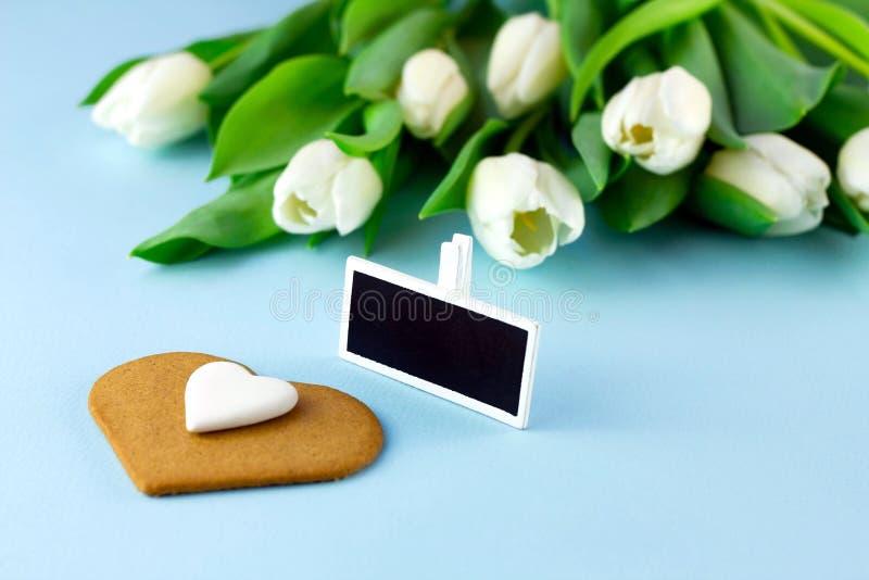 Тюльпаны, бирка подарка с космосом экземпляра и печенье в форме сердца на голубой предпосылке стоковые фотографии rf