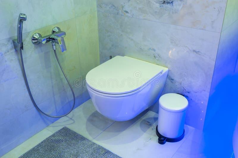 Туалет и деталь углового биде ливня с распределителями мыла и шампуня на приложении ливня держателя стены в неоновом свете стоковые фото