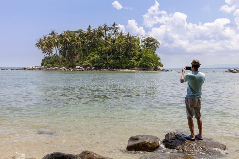 Туристский человек стоя на камне в сезоне лета и принимает фото красивый малый остров в Пхукете Таиланде стоковые изображения