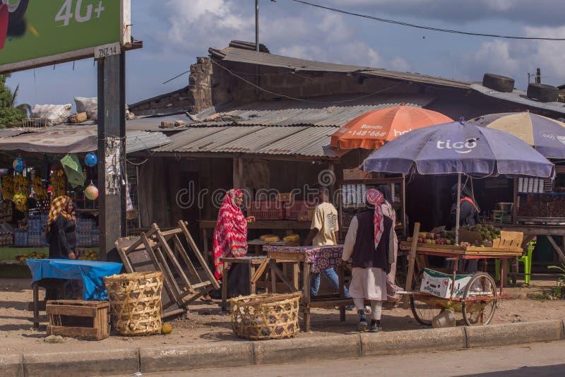 Туристы и locals на национальном рынке Африканский человек идя вниз по улице стоковые фото