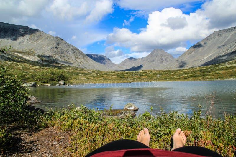 Турист лежит видимое тело и ноги на том основании отдыхая от тяжелый trekking обозревающ озеро в горах Khibiny, Ru стоковые изображения rf