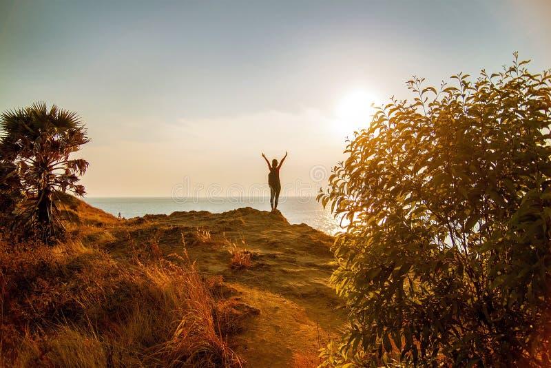 Турист при рюкзак стоя на морском побережье с поднятыми руками стоковая фотография rf