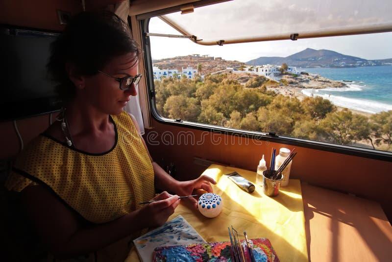 Турист продолжает его хобби, картину утесов, с красивой предпосылкой греческого острова Paros стоковое фото rf