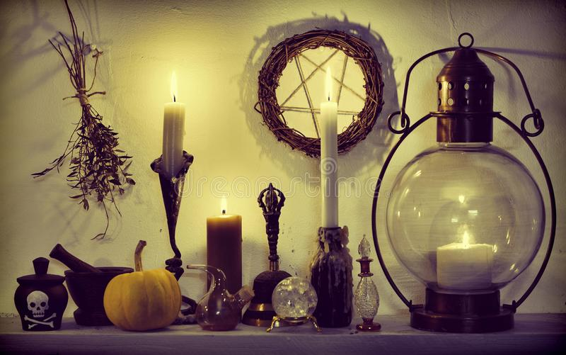 Травы, тыква, кристаллы, винтажная лампа и пентаграмма на таблице ведьмы стоковые фото