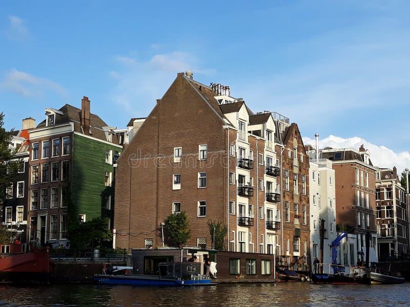 Традиционные старые здания и шлюпки вдоль каналов Амстердама в центре города Амстердама, Нидерланд стоковое фото rf