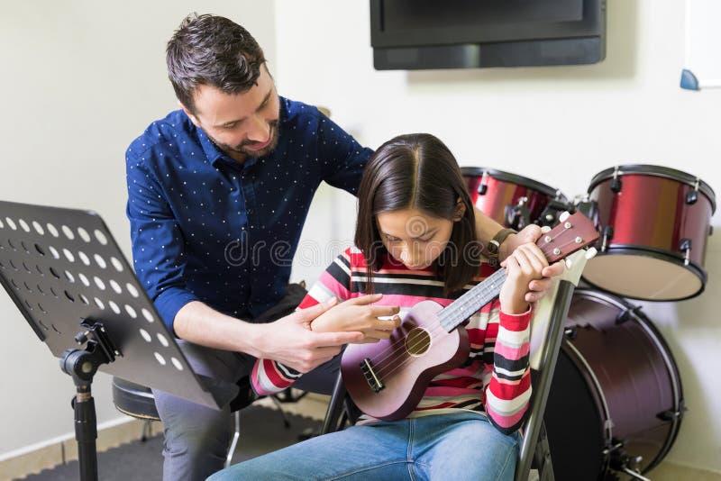 Тренер помогая предназначенному для подростков студенту в игре гавайской гитары стоковые фотографии rf