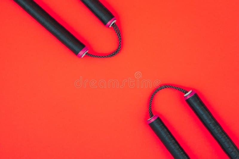 Тренируя nunchaku изолированное на красной предпосылке Оружие Nunchaku азиата на красной предпосылке и место для текста стоковое изображение rf