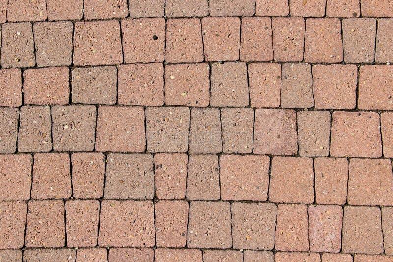 Тротуар вымощенный с незаконными trapeziform оранжевыми плитками стоковое фото