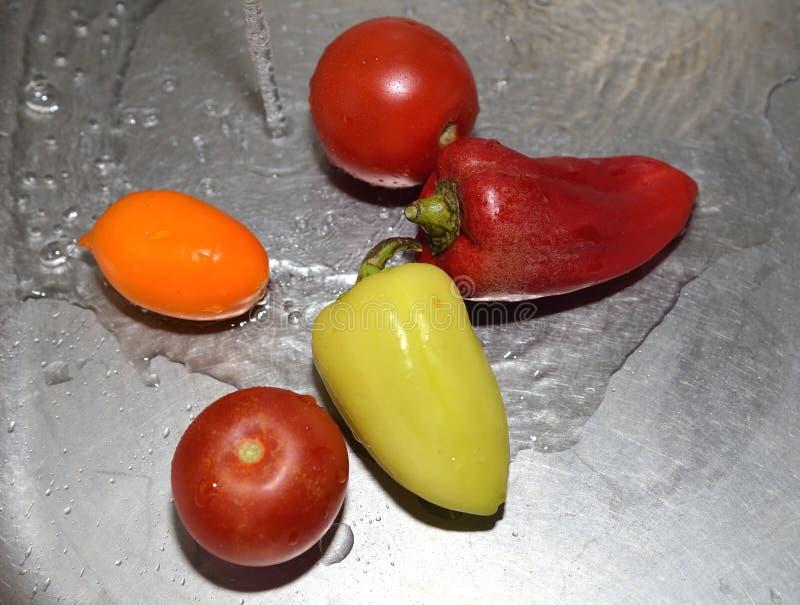Томаты и перцы под проточной водой в кухонной раковине стоковое фото