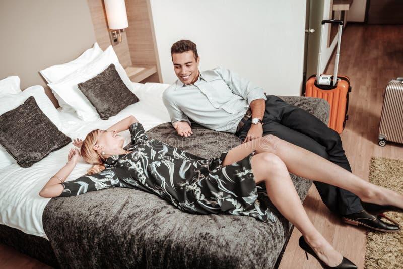 Тонкая жена нося стильное платье лежа на кровати около супруга стоковое изображение rf