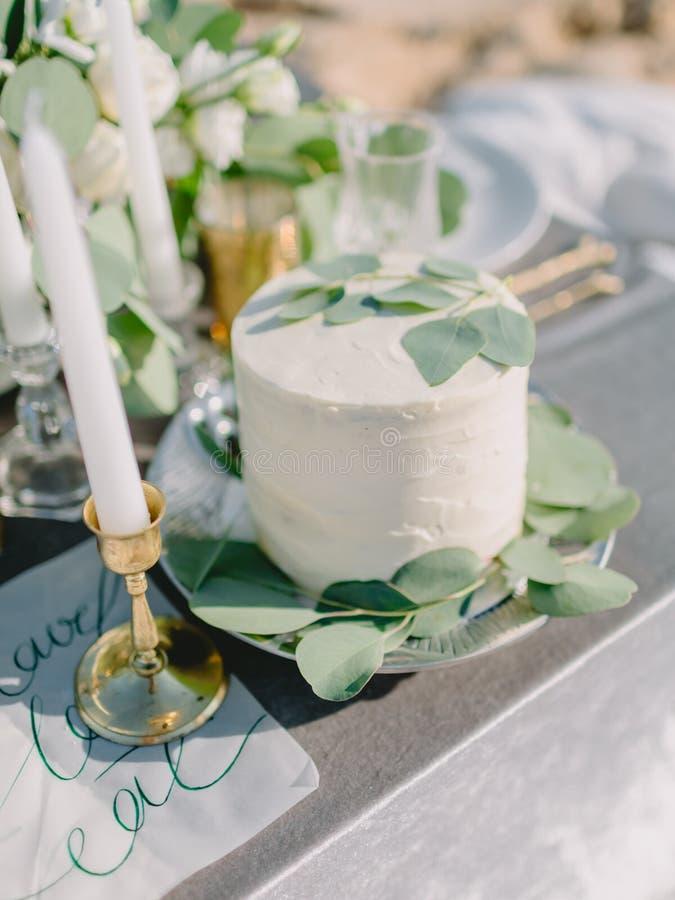Торт свадьбы сладкий со сливками и листья эвкалипта для украшения Обедающий свадьбы стоковое фото