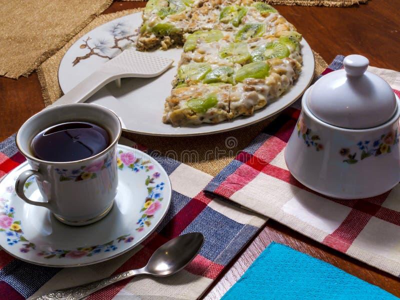 Торт сделанный из печениь, украшенных с кусками кивиа, лож в белой плите рядом с поддонником и чашкой черного чая на checkered стоковые изображения
