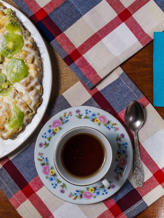 Торт сделанный из печениь, украшенных с кусками кивиа, лож в белой плите рядом с поддонником и чашкой черного чая на checkered стоковые изображения rf