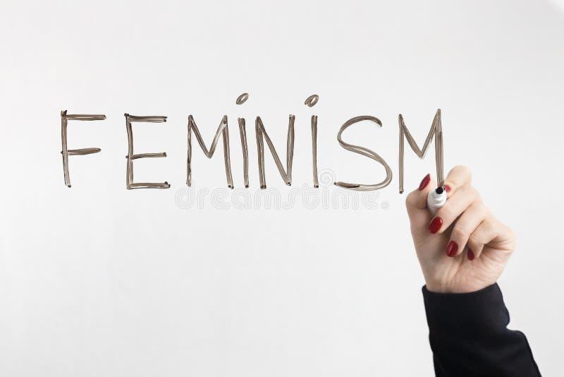 ФЕМИНИЗМ слова написанный на стеклянной доске с женской рукой стоковое изображение rf