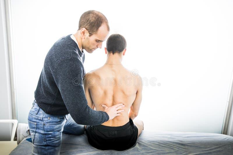 Физиотерапевт рассматривая молодого человека назад Концепция физиотерапии стоковая фотография rf