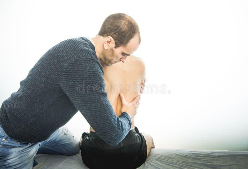 Физиотерапевт рассматривая молодого человека назад Концепция физиотерапии стоковое фото