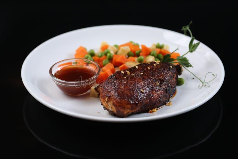 Филе цыпленка, испеченное со специями и покрытое с аппетитной коркой, на плите с овощами и соусом стоковое фото