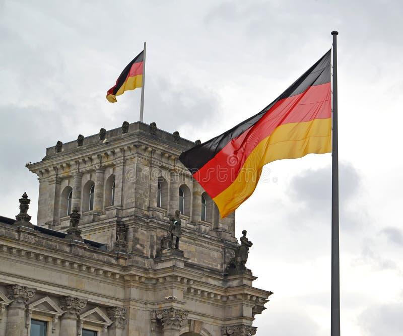 Флаг Германии порхает на фоне здания Reichstag beriberi стоковые изображения rf