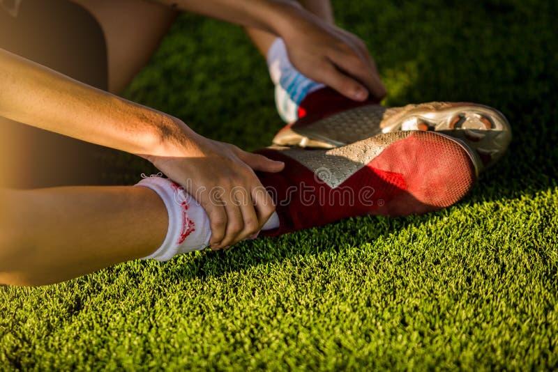 Футболисты сидят и улавливают подошвы ног из-за боли стоковое изображение rf
