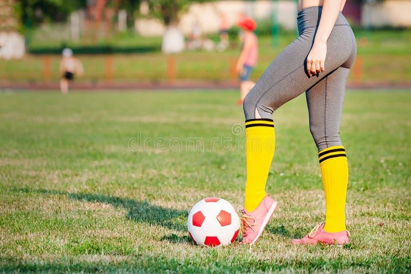 Футболист молодой женщины с шариком на поле стоковые фото