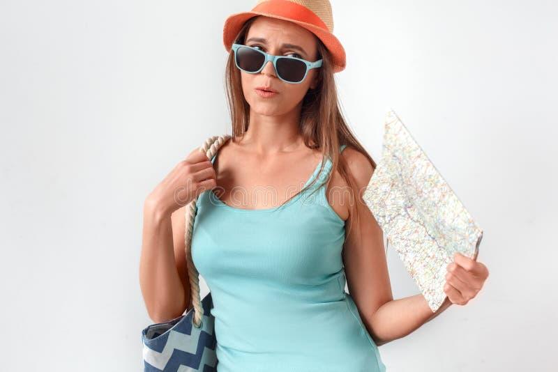 фристайл Женщина в студии положения шляпы изолированной на белизне с вентилятором сумки пляжа с чувством карты горячим стоковая фотография rf
