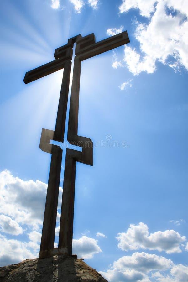 Фото конца-вверх металла правоверного перекрестного в проекции против голубого неба с облаками и ярким крестом слепимости солнца стоковая фотография