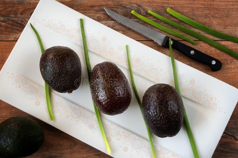 Фото конца-вверх свежих всех авокадоов и свежего лука в белом блюде фарфора на коричневой деревянной предпосылке стоковые фото