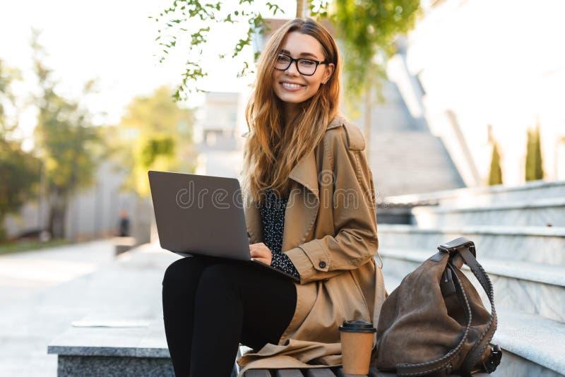 Фото довольной женщины работая на ноутбуке пока сидящ на стенде в улице города стоковое фото