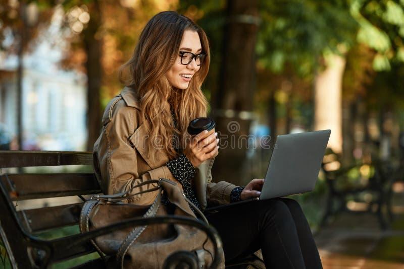 Фото довольной женщины работая на ноутбуке пока сидящ на стенде в sunlit переулке стоковое фото