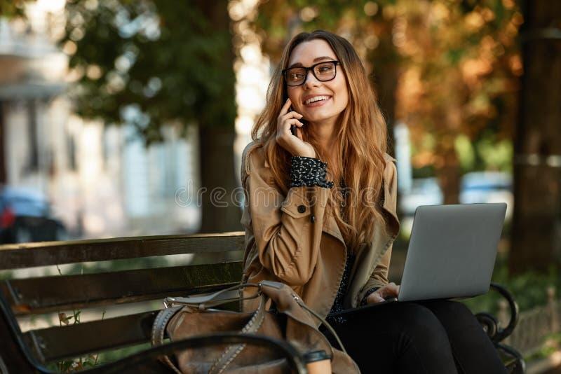 Фото довольной девушки используя мобильный телефон и ноутбук пока сидящ на стенде в sunlit переулке стоковое фото