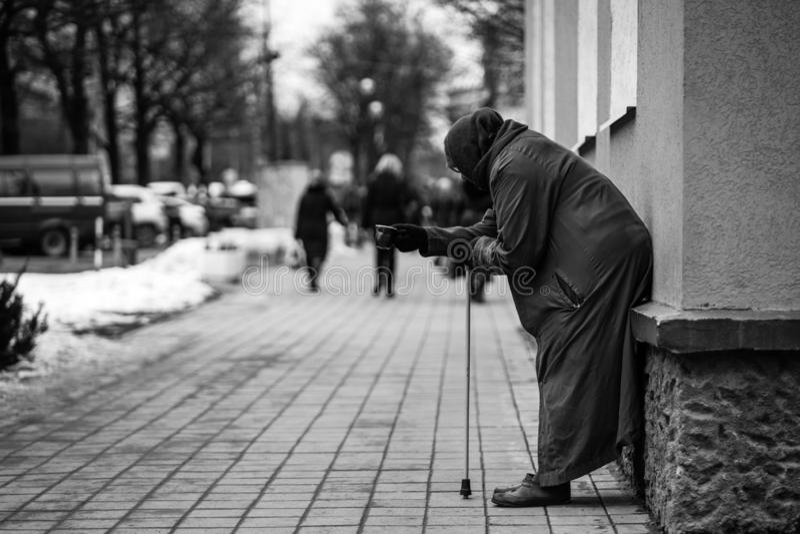 Фото старого голодного бездомного женского попрошайки умоляет для милостынь и на улице стоковые фотографии rf
