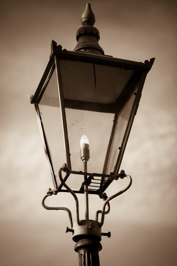 Фото Sepia ретро уличного фонаря светя против предпосылки облачного неба стоковые фото