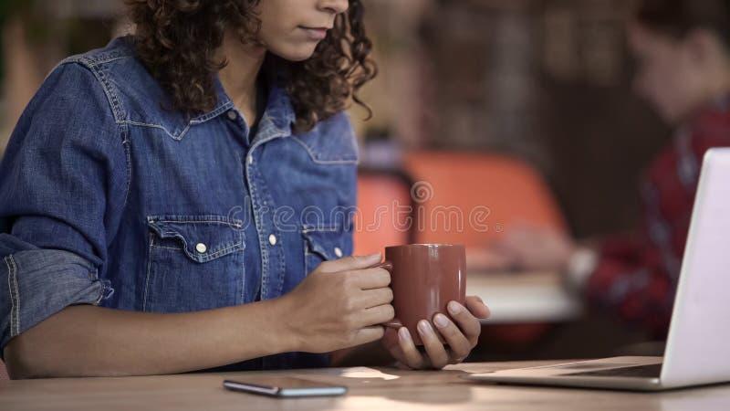 Чай Biracial молодой женщины выпивая и наблюдая видео на ноутбуке, устройствах стоковые изображения rf