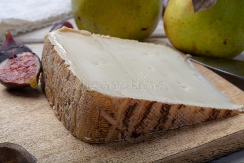 Часть французского сыра Tomme de Brebis сделала из молока овец, который служат как десерт со свежими смоквами и грушами стоковые изображения rf