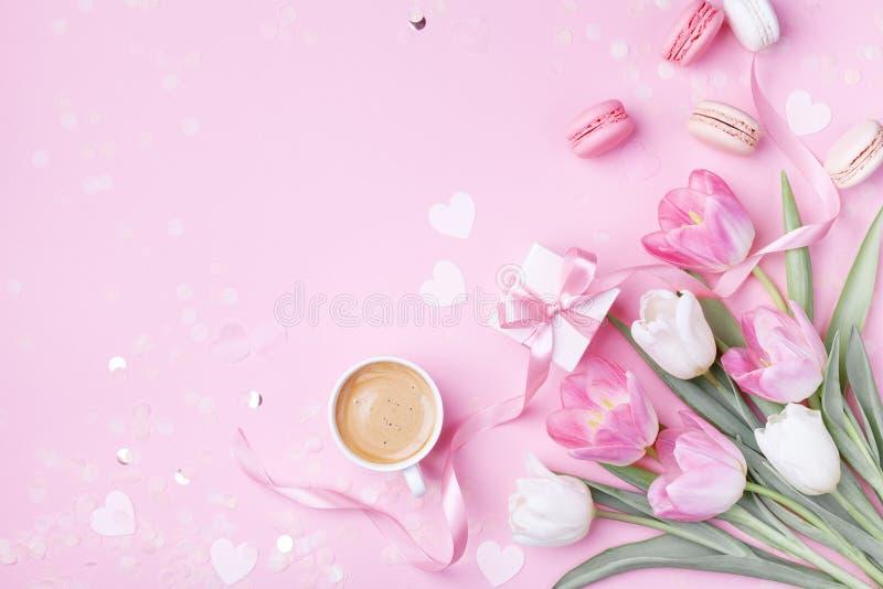 Чашка кофе утра, macaron торта, подарочная коробка и цветки тюльпана весны на розовой предпосылке Красивый завтрак на день женщин