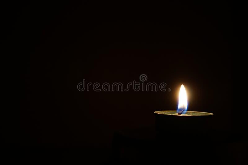 Чашка свечи воска в темноте, свете свечи в черной предпосылке стоковое фото