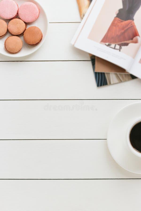 Чашка черного кофе на белом деревянном столе с журналом о моде и macaroons Автор обрабатывая, влияние фильма стоковое фото rf