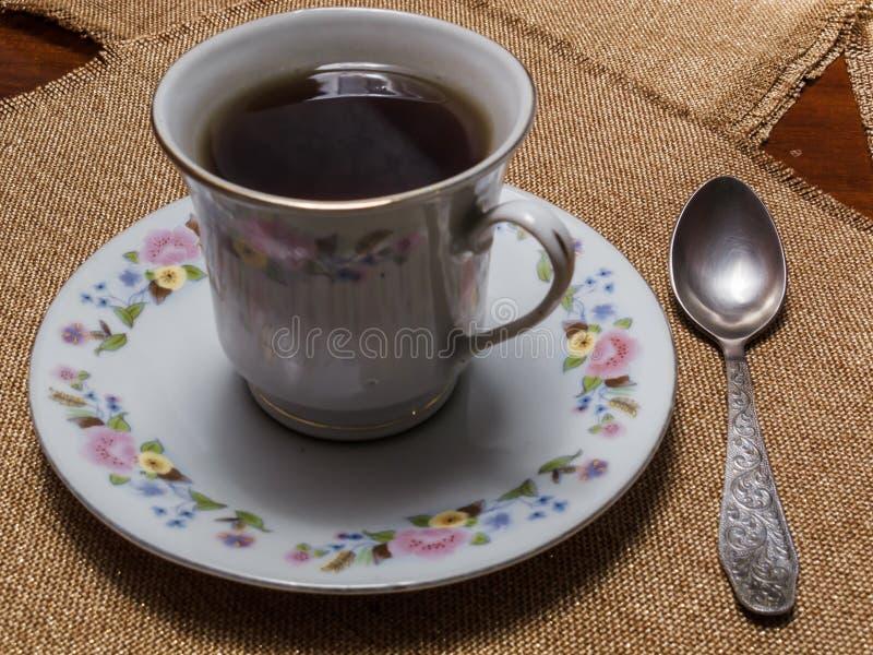 Чашка черного чая на поддоннике на таблице с салфетками стоковое фото rf