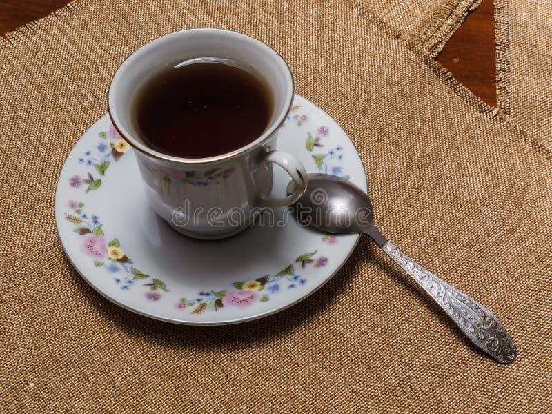 Чашка черного чая на поддоннике на таблице с салфетками стоковые фотографии rf